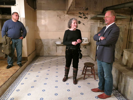 Panama Hotel owner Jan Johnson describing the bathhouse in the basement. Shown with Michael Sullivan, Principal, Artifacts Consulting, Inc. (right) and Horace Foxall, Jr. (left), historic architect and past member of the Board of Advisors for Washington State, National Trust for Historic Preservation. / Photo: Eugenia Woo